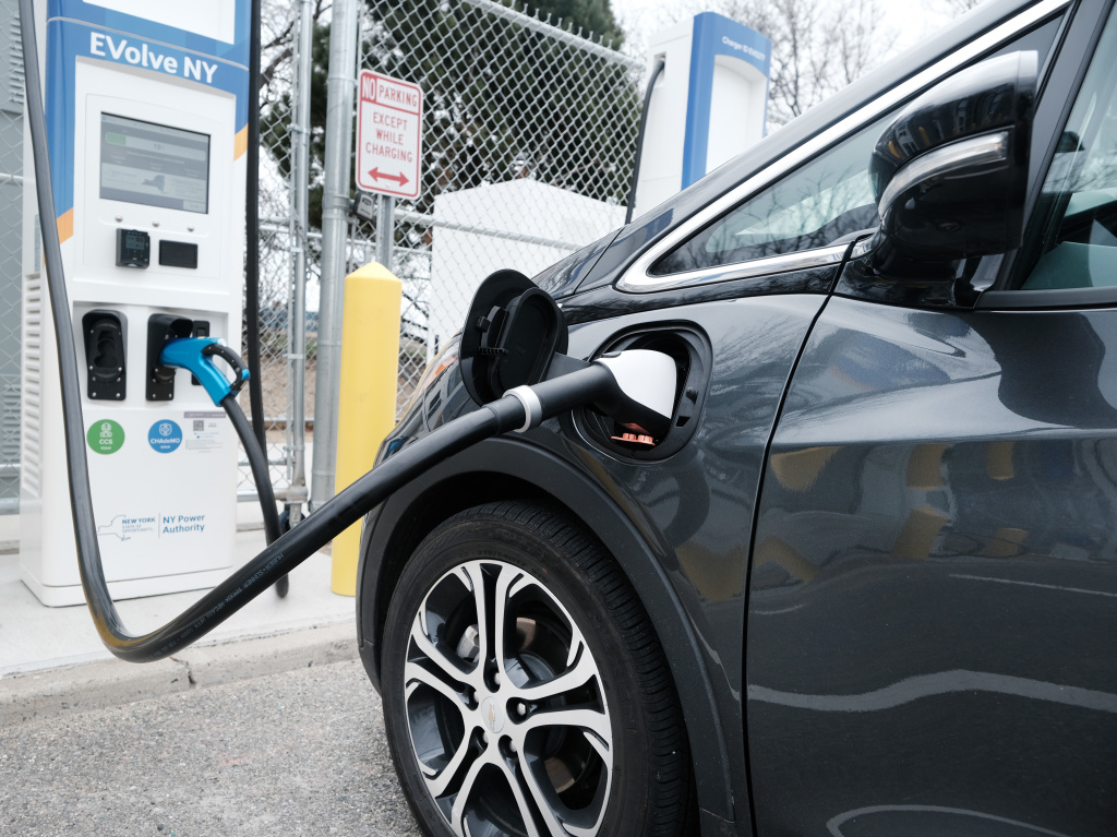 A driver uses a fast-charging station for electric vehicles at John F. Kennedy airport on April 2. As part of President Biden's $2 trillion infrastructure plan, $174 billion would go to supporting the production of electric vehicles in the U.S.