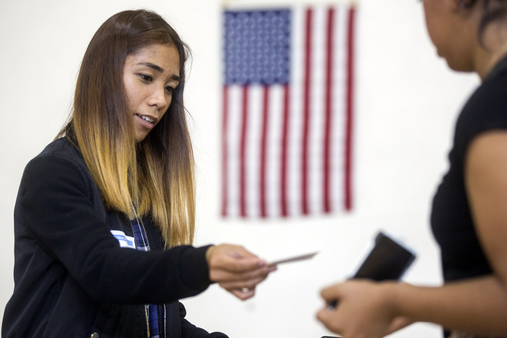 Poll worker Ceanne Agustin hands a voter their ballot receipt at a polling place inside Barrio Action Youth & Family Center in El Sereno on Tuesday afternoon, June 7, 2016 during the California primary election.