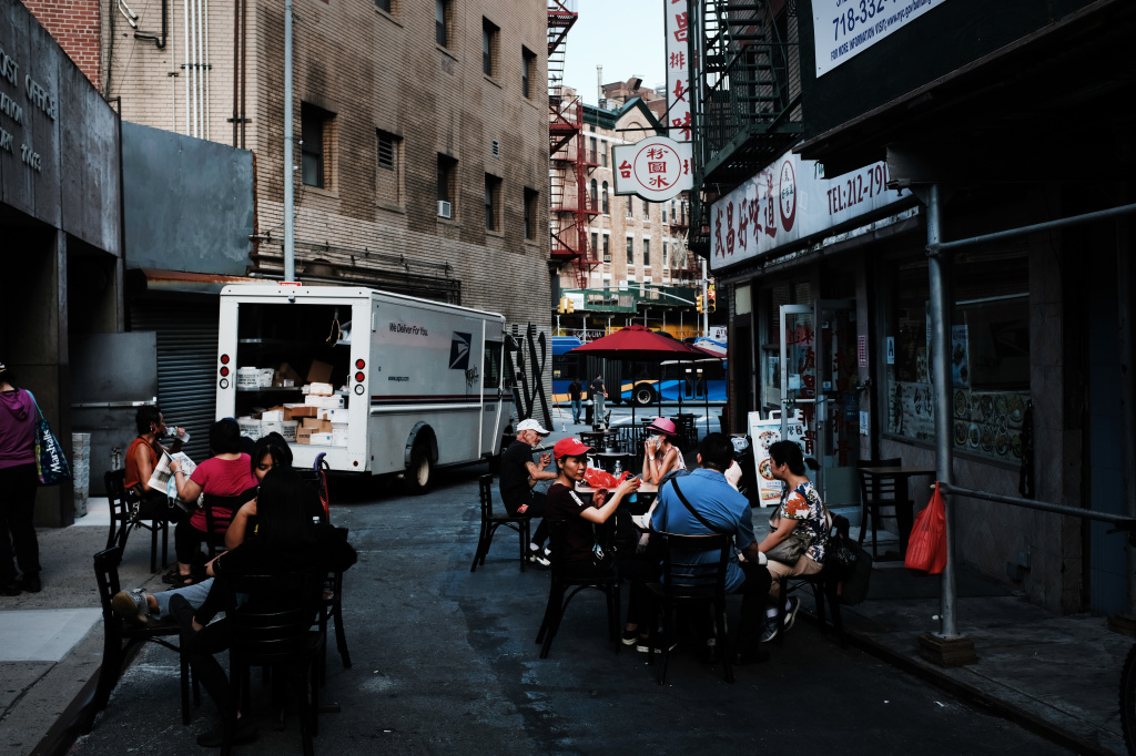 People eat in an outdoor dining area in New York City's Chinatown on Aug. 10. Economists warn spending may suffer this month.