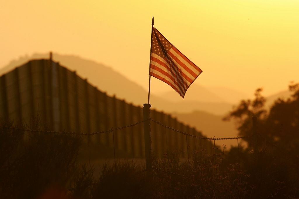 A U.S. flag put up by activists who oppose illegal immigration flies near the US-Mexico border fence in an area where they search for border crossers October 8, 2006 near Campo, California. The activists want the fence expanded into a fully-lit double-fenced barrier between the US (R) and Mexico. US Fish and Wildlife Service wardens and environmentalists warn that a proposed plan by US lawmakers to construct 700 miles of double fencing along the 2,000-mile US-Mexico border, in an attempt to wall-out illegal immigrants, would also harm rare wildlife. Wildlife experts say cactus-pollinating insects would fly around fence lights, birds that migrate by starlight in the desert wilderness would be confused, and large mammals such as jaguars, Mexican wolves, Sonoran pronghorn antelope, and desert bighorn sheep would be blocked from migrating across the international border, from California to Texas.