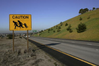 A sign is posted near the border between U.S. and Mexico warning drivers of immigrants crossing the freeway in San Ysidro, CA on January 24, 2006.