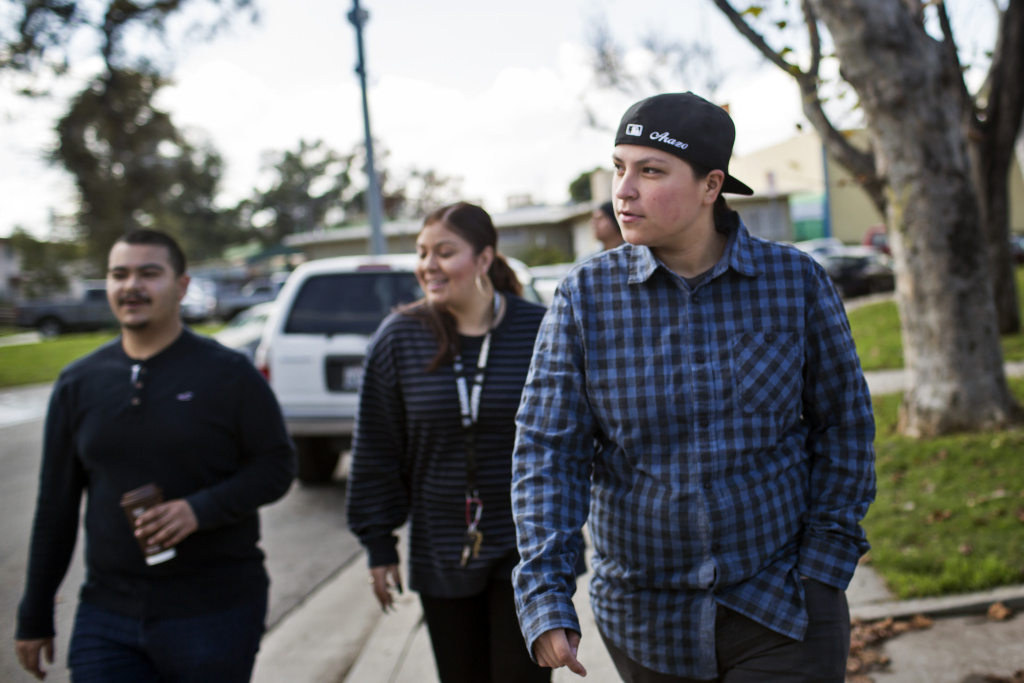 Ramona Gardens residents Eddie Licon, left, Amanda Gutierrez and Marlene Arazo, walk through the public housing development  in Boyle Heights operated by the Housing Authority of the City of Los Angeles on Friday, Jan. 13, 2017. There are six different surrounding gangs in the neighborhood where they grew up.