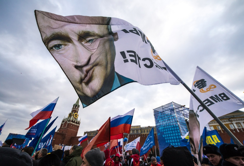 With a flag depicting President Vladimir Putin (C) pro-Kremlin activists rally at the Red Square in Moscow, on March 18, 2014, to celebrate the incorporation of Crimea. Putin pushed today every emotional button of the collective Russian psyche as he justified the incorporation of Crimea, citing everything from ancient history to Russia's demand for respect to Western double standards.