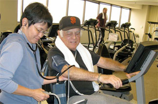 Actor Jonathan Haze bicycles at the Cardiac Rehab Lab at Cedars-Sinai Heart Institute. Exercise physiologist Asako Oshiro takes his blood pressure while he's pumping.