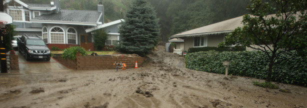 Mud flows between houses and into the street in an evacuated neighborhood during the fourth storm of the week on January 21, 2010 in La Canada Flintridge, California.