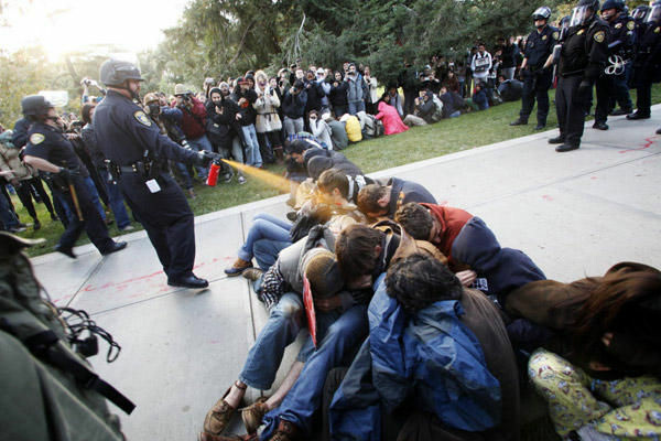 In this Friday, Nov. 18, 2011, photo University of California, Davis Police Lt. John Pike uses pepper spray to move Occupy UC Davis protesters while blocking their exit from the school's quad Friday in Davis, Calif. Two University of California, Davis police officers involved in pepper spraying seated protesters were placed on administrative leave Sunday, Nov. 20, 2011, as the chancellor of the school accelerates the investigation into the incident.