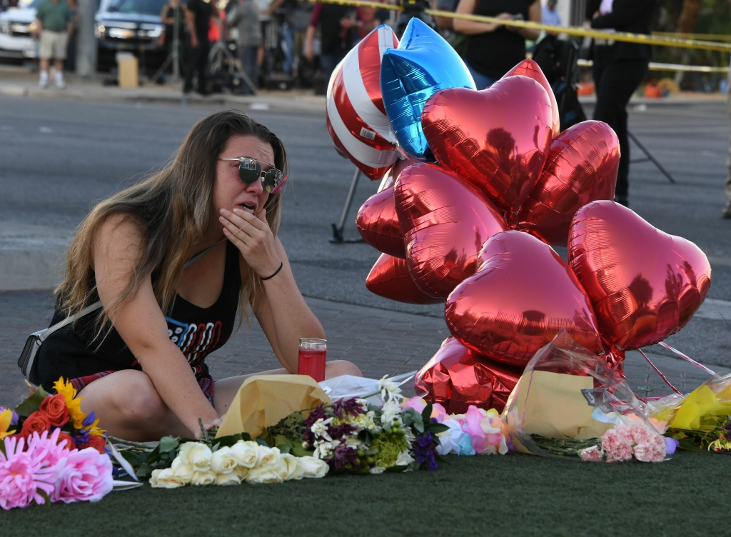 Destiny Alvers, who attended the Route 91 country music festival and helped rescue her friend who was shot, reacts at a makeshift memorial on the Las Vegas Strip.