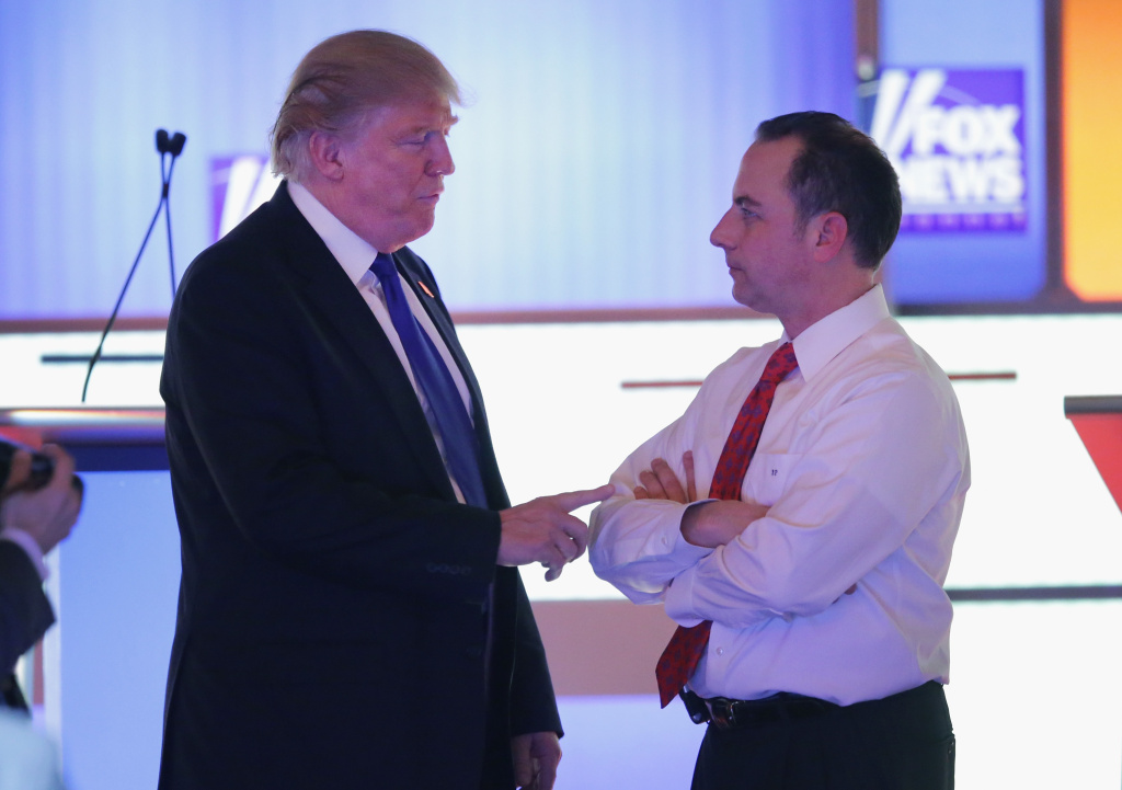 Republican presidential candidate Donald Trump (L) speaks with Reince Priebus, chairman of the Republican National Committee, at a debate at the Fox Theatre on March 3, 2016 in Detroit, Michigan.