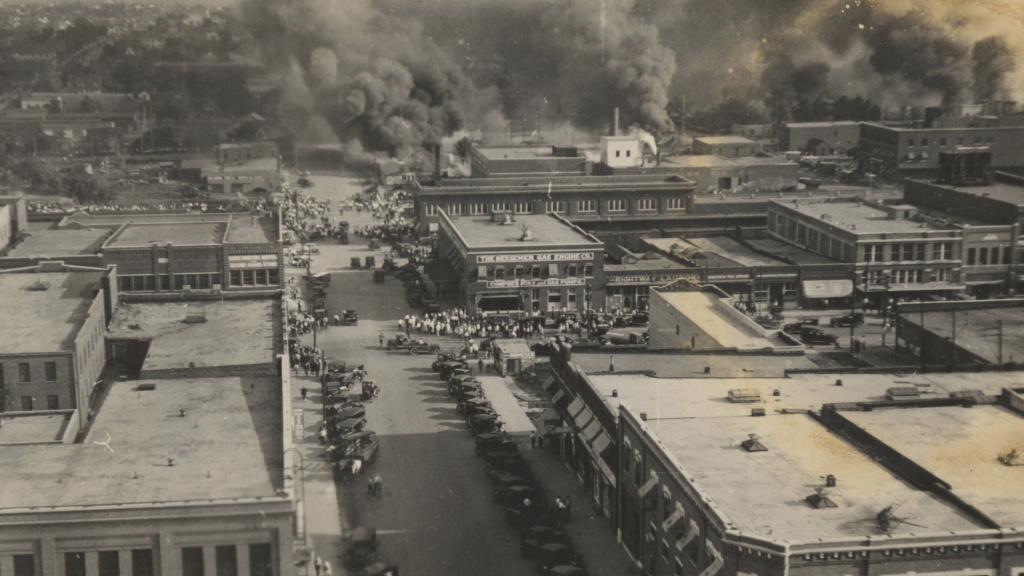 This archival photo shows crowds of people watching fires during the June 1, 1921, Tulsa Race Massacre.