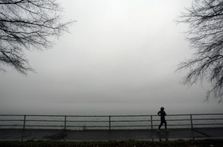 A jogger disappears into the fog along the Potomac River.