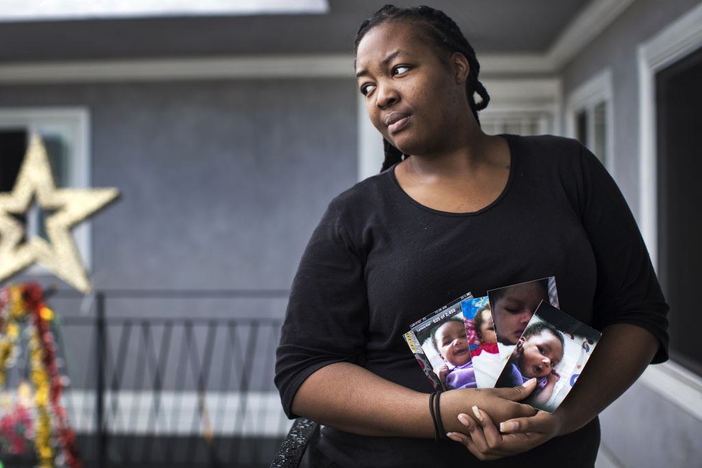 Daejanae Marshall holds photographs of her baby daughter, Zah'Nyah, outside her South Los Angeles home on Friday, Dec. 30, 2016.