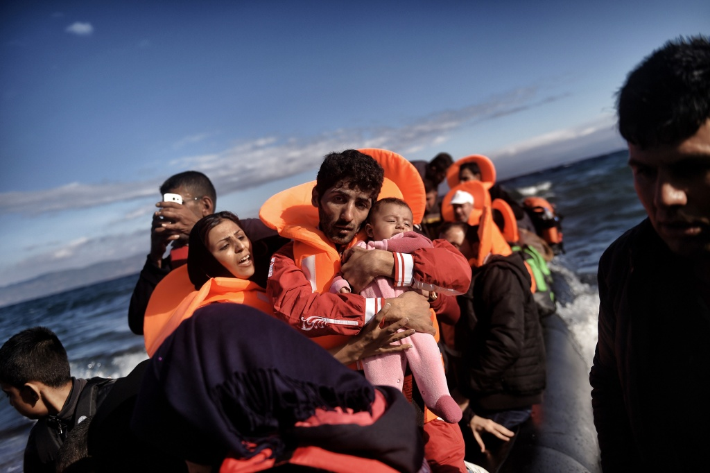 A man wearing an orange life jacket holds an infant as refugees and migrants arrive on the Greek island of Lesbos after crossing the Aegean sea from Turkey on October 1, 2015.