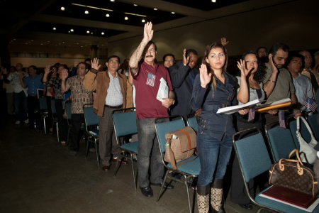 New U.S. citizens take their oath at a naturalization ceremony at the Los Angeles Convention Center. The mayors of Los Angeles, New York and Chicago are kicking off an initiative to encourage more legal permanent residents to become citizens.
