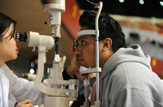 Domingo Andrade (R) gets an eye exam at a free clinic sponsored by Remote Area Medical (RAM), a Tennessee-based nonprofit, in Los Angeles on April 28, 2010.
