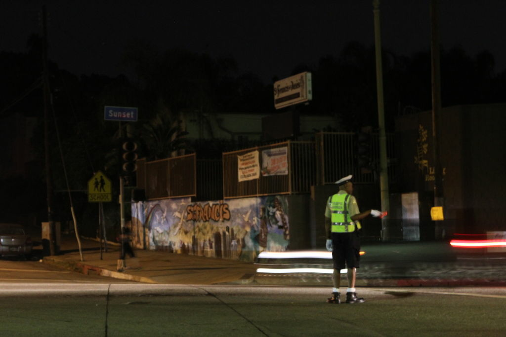 A Traffic officer keeps the intersection of Sunset and Maltman safe during Silver Lake's second power outage in one day.