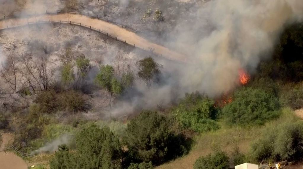 Firefighters battling brush fire near homes in Orange County.