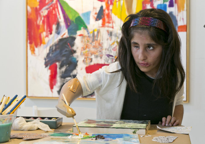 Afghan war victim Shah Bibi Tarakhail uses her new prosthetic arm to paint during a private session with artist Dayvd Whaley at Galerie Michael in Beverly Hills, Calif., Wednesday, April 2, 2014. Shah Bibi, a 7-year-old Afghani who lost her arm after picking up a grenade, received a new prosthetic arm at Shriners Hospital for Children and will be heading back home to her family on April 8, though she will return to Southern California in coming summers for additional medical procedures, including receiving a prosthetic eye.