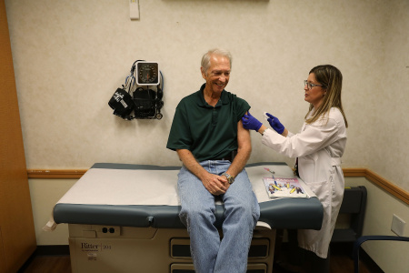 Stuart Goldstein receives an influenza vaccination from nurse practitioner, Katherine Male, at the CVS Pharmacy store's MinuteClinic on October 4, 2018 in Miami, Florida.