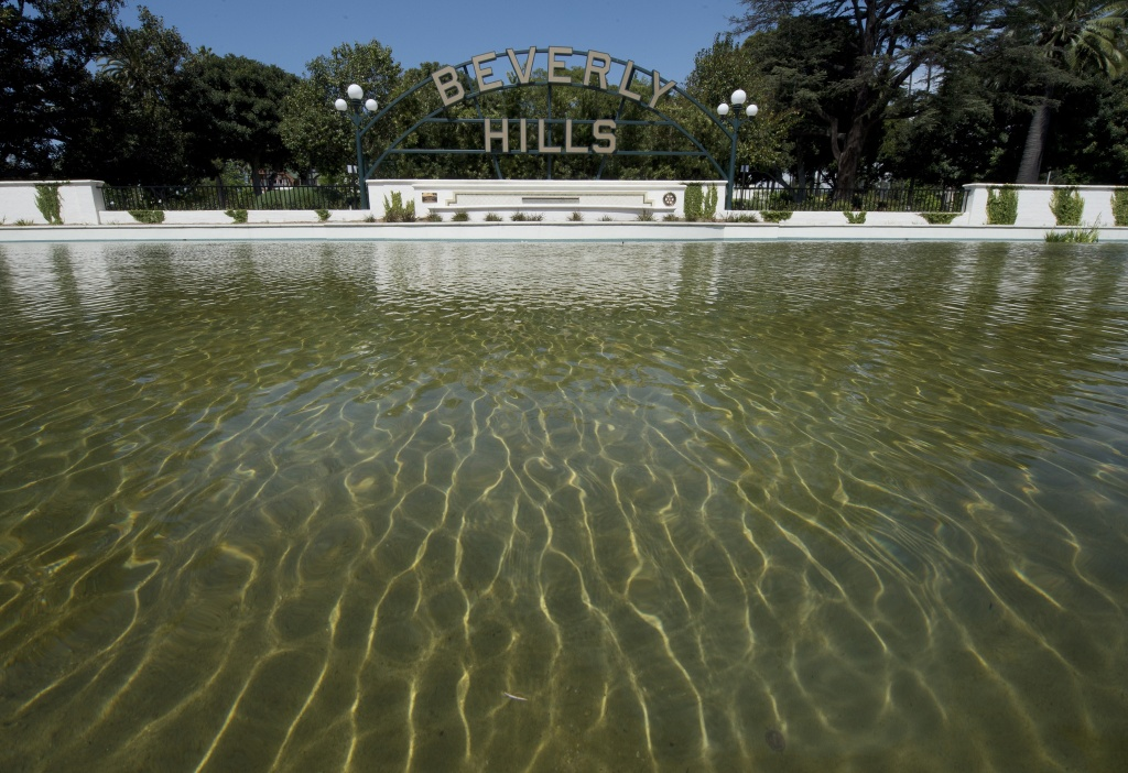 The Beverly Hills lily pond with the city's famous sign is seen during a severe drought in Beverly Hills,  California in this April 9, 2015 file photo. Four water suppliers, including Beverly Hills, have consistently failed to meet their savings targets and were among the first to be fined, the State Water Resources Control Board said Friday.