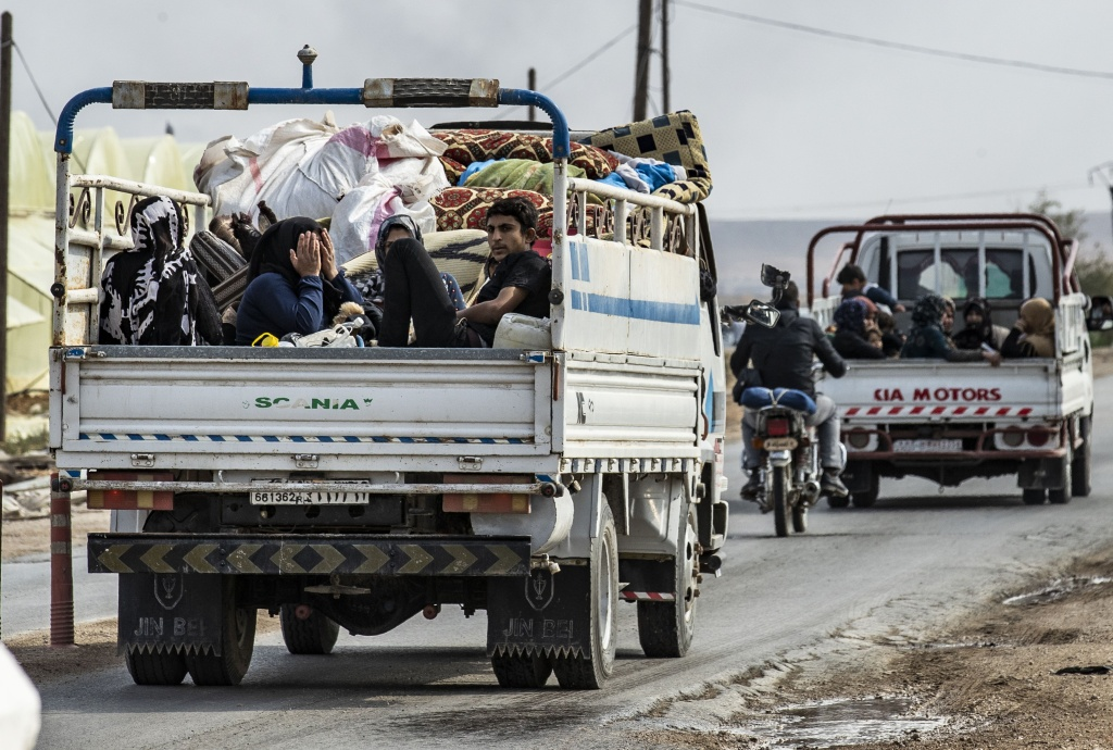 Syrians flee with their belongings the countryside of the northeastern Syrian town of Ras al-Ain on the Turkish border, toward the west to the town of Tal Tamr on October 19, 2019.