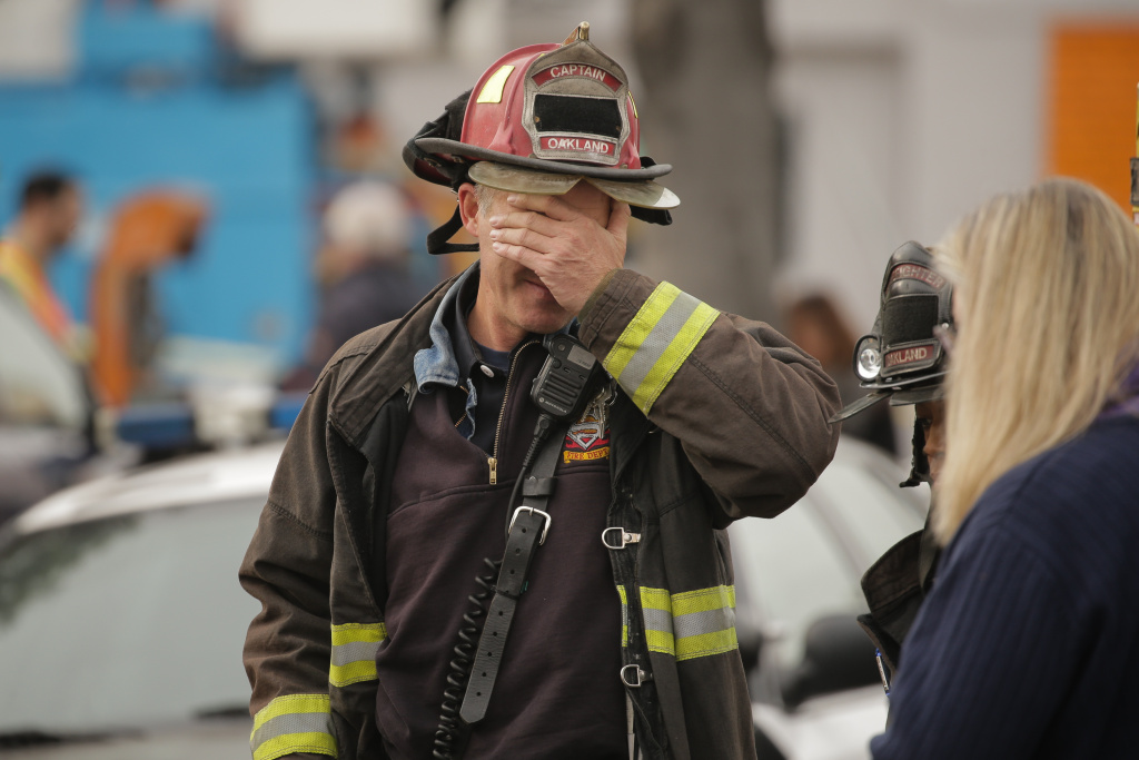 OAKLAND, CA - DECEMBER 05: Oakland fire captain Chris Foley wipes his brow at the site of a warehouse fire that has claimed the lives of at least thirty-six people on December 5, 2016 in Oakland, California. The fire took place during a musical event late Friday night. (Photo by Elijah Nouvelage/Getty Images)