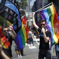 A man carries a rainbow flag and whistle at the LA Pride Parade on June 8, 2014 in West Hollywood, California.