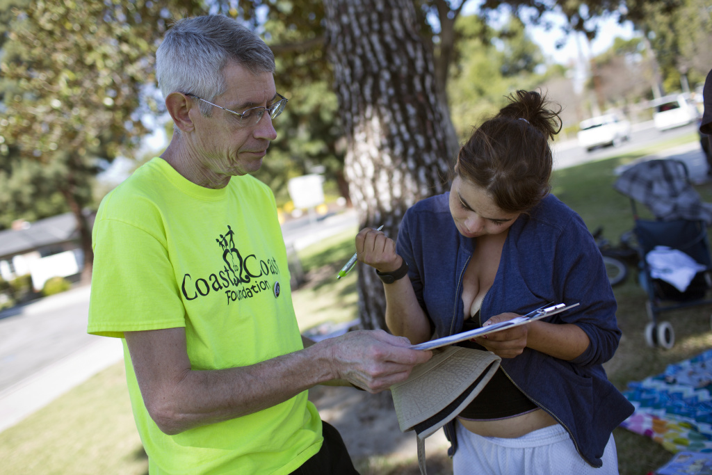 Volunteer Philip Armstrong, left, works with Julia Lewis, 20, during a weekly outreach assessment put on by the Coast to Coast Foundation in partnership with the Fullerton Police Department on Thursday, March 5, 2015 at Pacific Drive Park. Lewis is from New Jersey and has been homeless in Orange County for four years.