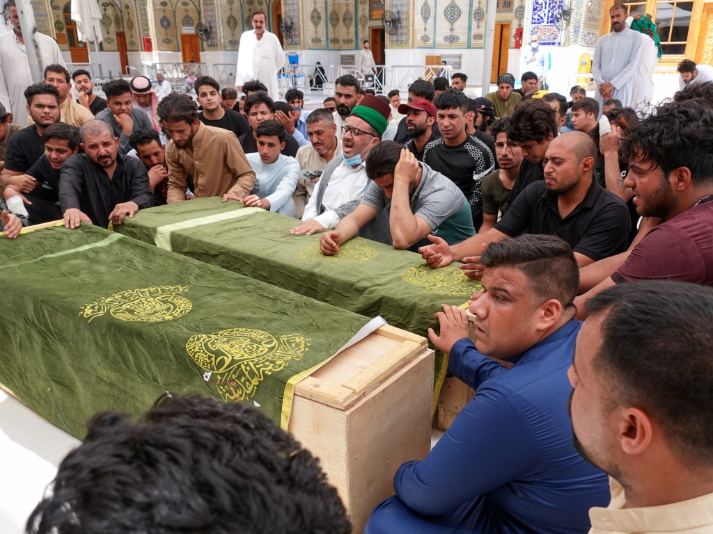 Iraqis in the holy shrine city of Najaf on Sunday mourn relatives killed during a massive fire at a Baghdad hospital dedicated to COVID-19 patients.