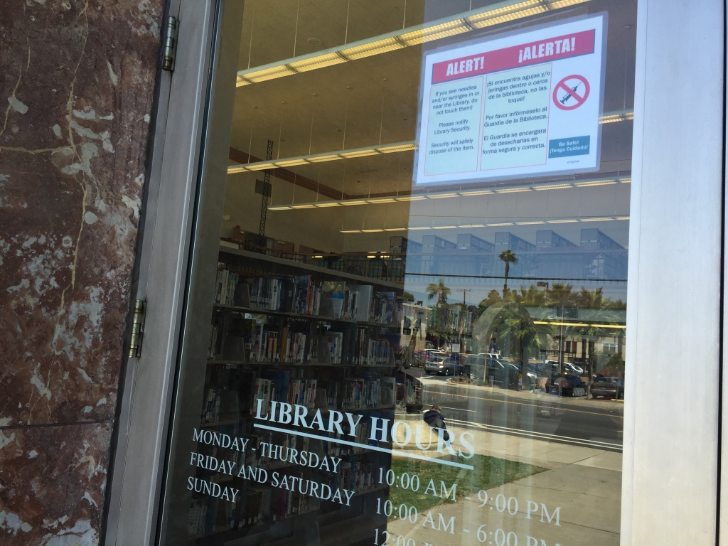 A sign on the entrance of the Santa Ana Public Library warns patrons not to pick up needles or syringes. Library operations manger Heather Folmar said she has noticed them around the library grounds.