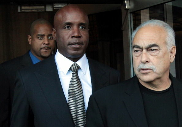 Former Major League Baseball player Barry Bonds (C) is flanked by security guards as he leaves federal court following a sentencing hearing on December 16, 2011 in San Francisco, California.
