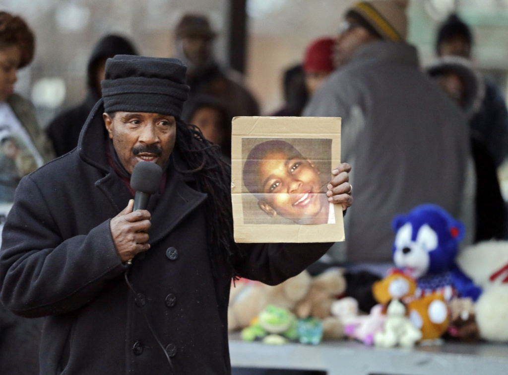 Activist Art McCoy holds a photo of Tamir Rice before a protest march at Cudell Park in Cleveland, Monday, Nov. 24, 2014. The 12-year-old was fatally shot by a Cleveland police officer last year after he reportedly pulled a replica gun at the city park.