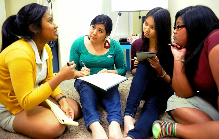 "Community organizer Ashley Uyeda (second from the left) listens during a group youth session at the Khmer Girls in Action offices in Long Beach. Many of the girls' parents immigrated in the early 1980s after fleeing the ""killing fields"" of the Khmer Rouge regime, a genocide that resulted in an estimated 1.7 to 2 million deaths."