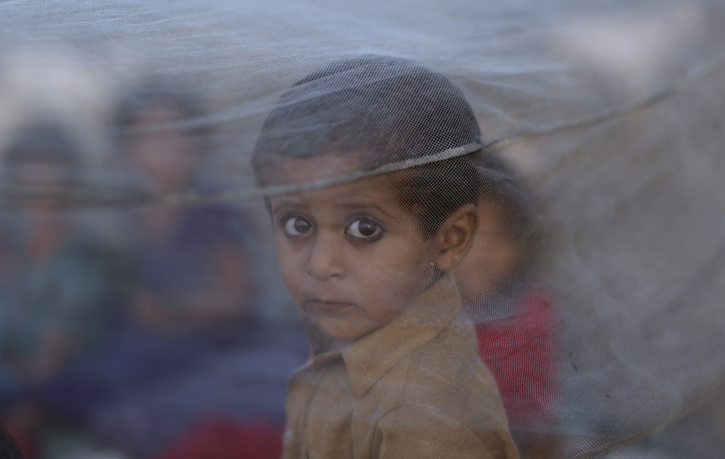 In this file photo, Pakistani boy peers out from behind a mosquito net after his family fled their home due to catastrophic flooding in Sindh province. The World Health Organization projects an additional 250,000 deaths a year, starting in 2030, due to diseases like malaria and diarrhea.