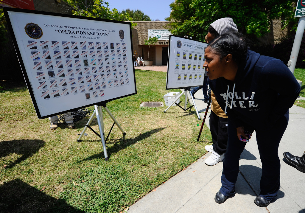 People from the neighborhood of Baldwin Hills Village look at posters showing faces of 75 members and associates of alleged