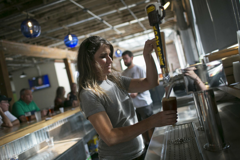 Molly Mattin pours beer at Mother Stewart's Brewing in Springfield. The new brewery, located in an old warehouse space, is part of the city's downtown revival which includes new shops and a farmer's market.