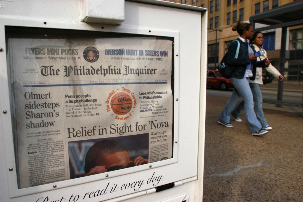 Pedestrians walk past a newspaper vending machine as it lies next to the PNI Building, which houses the Philadelphia Inquirer and Daily News.
