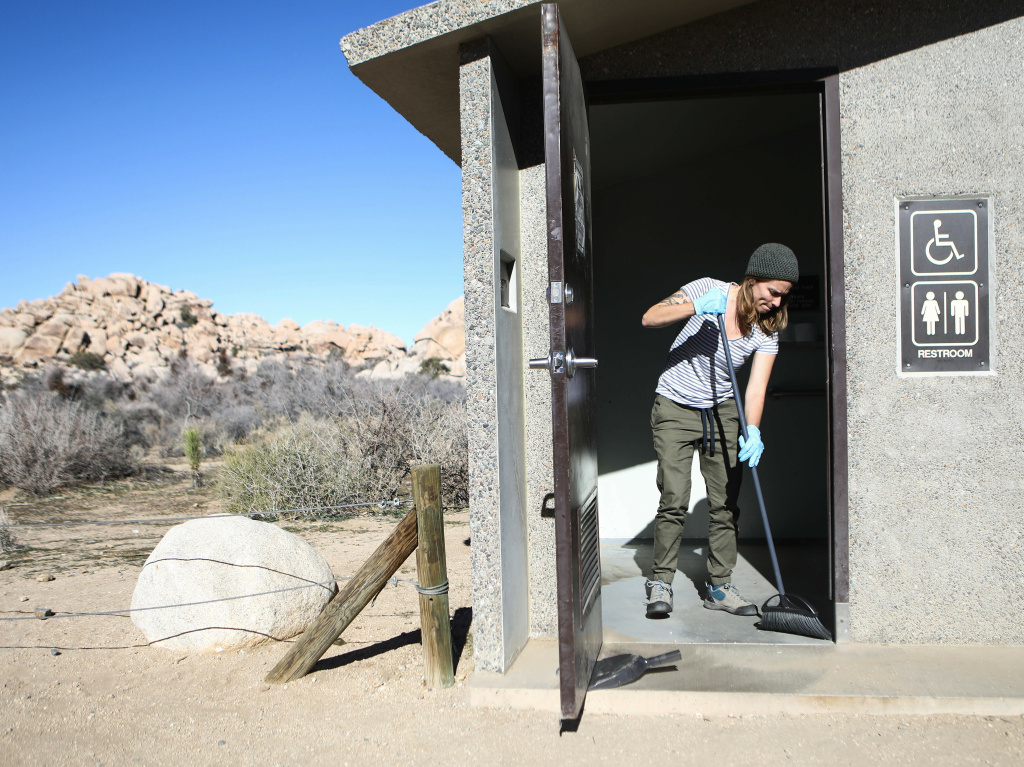 Volunteer Alexandra Degen cleans a restroom during the government shutdown at Joshua Tree National Park in California.