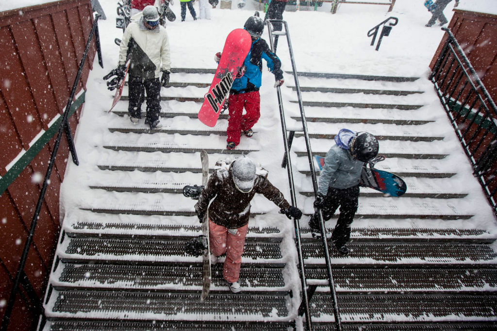 Skiers and snowboarders come back from the slopes at Bear Mountain Lodge.
