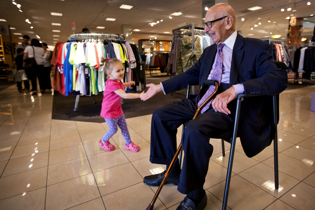 Ted DiNunzio high-fives 2-year-old Zoey at the Nordstrom store in Arcadia on Sept. 20. DiNunzio works at the store as a greeter every Friday and Saturday.