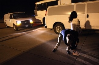 An Immigration and Customs Enforcement (ICE), officer prepares an undocumented Salvadoran immigrant for a deportation flight bound for San Salvador.
