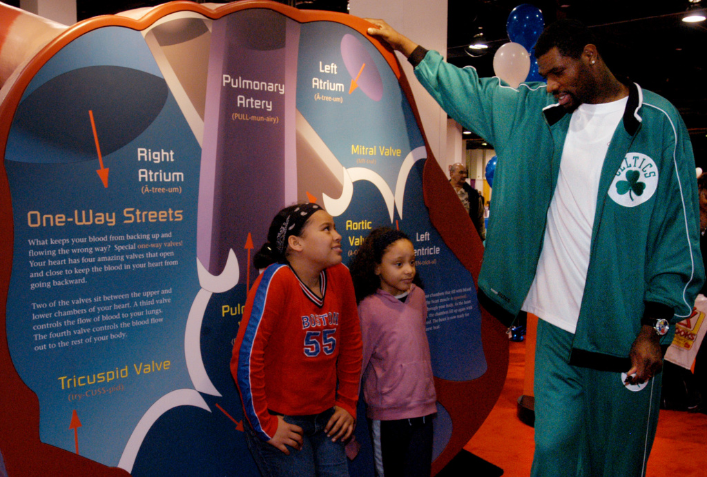 File: Natalia Toledo, 11, left, and her cousin Shayla Toledo, 7, both of Boston, talk with Boston Celtics player Walter McCarty inside a model heart, part of the