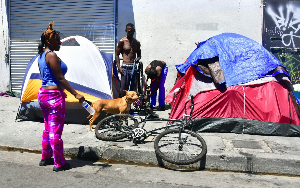 Homeless residents chat beside their tents on a street in downtown Los Angeles, California on June 25, 2018, as a United Nations report on poverty and inequality says 185 million Americans are living in extreme poverty