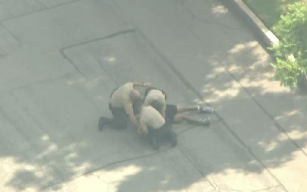 A screenshot showing deputies taking someone into custody. One of the deputies punched the man repeatedly.