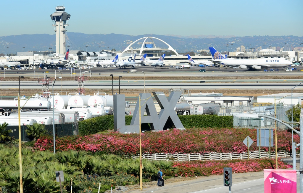 A traveller pulls his bags while walking past an LAX sign at Los Angeles International Airport as access roads were closed with flights delayed and cancelled after a gunman reportedly shot 3 people at a security checkpoint on November 1, 2013 in Los angeles, California.