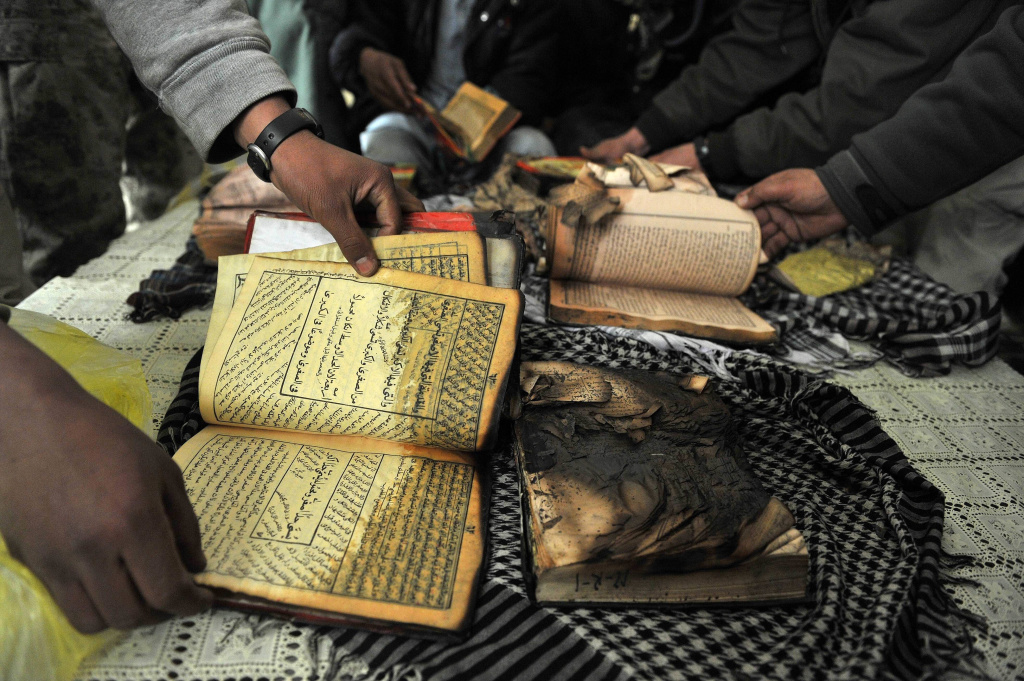 Afghan demonstrators show copies of Koran books allegedly set alight by US soldiers, during a protest against Koran desecration at the gate of Bagram airbase on February 21, 2012 at Bagram about 60 kilometres (40 miles) north of Kabul. Afghan protestors firing slingshots and petrol bombs besieged one of the largest US-run military bases in Afghanistan, furious over reports that NATO had set fire to copies of the Koran. Guards at Bagram airbase responded by firing rubber bullets from a watchtower, an AFP photographer said as the crowd shouted