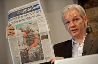 Australian founder of whistleblowing website, 'WikiLeaks', Julian Assange holds up a copy of The Guardian newspaper during a press conference in London on July 26, 2010.