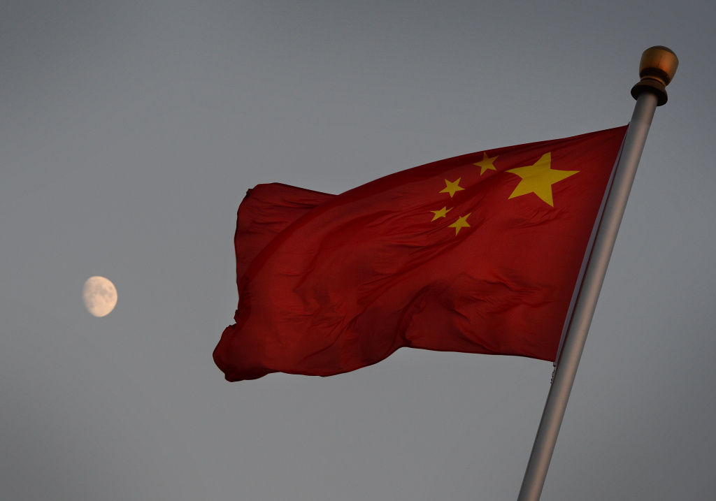The Chinese flag is seen in front of a view of the moon at Tiananmen Square in Beijing on December 13, 2013.