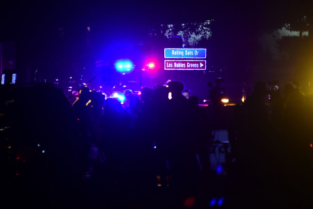 People gather as close as they can to the Borderline Bar and Grill in Thousand Oaks, California on November 8, 2018 as police vehicles closed off the area responding to a shooting