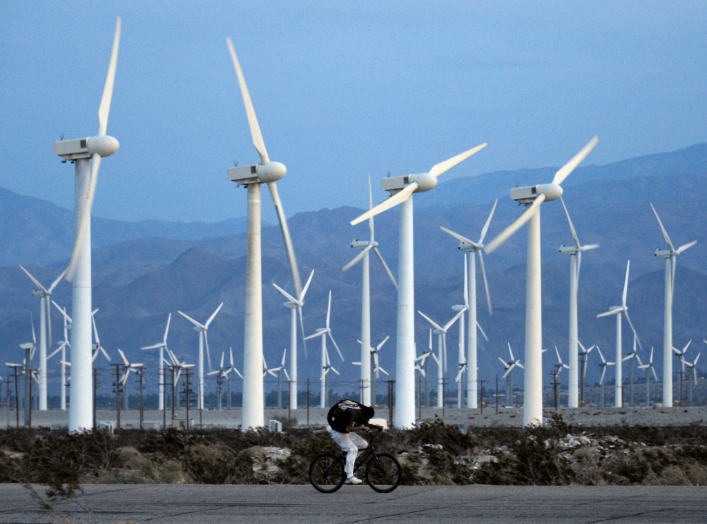 A man rids his bike against the win as giant wind turbines are powered by strong winds at sunset on March 27, 2013 in Palm Springs, California.
