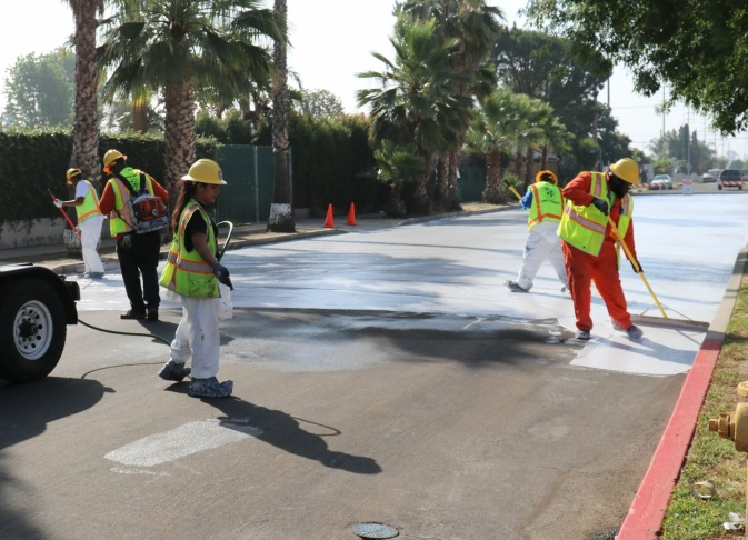 City employees paint a section of Beachy Ave in Pacoima a light gray on June 3, 2017 as part of a pilot project to test out